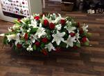 a classic red and cream lilly coffin spray  fresh  funeral flowers local and surrounding areas